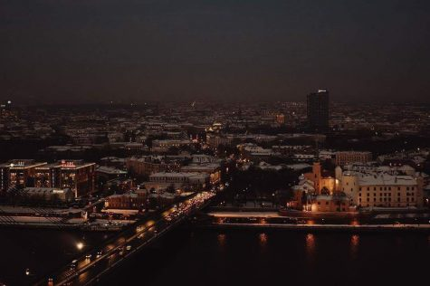Latvia's capitol city of Riga is shown at night time. The relative dimness of the city's lights compared to a typical American city shows how traditional the country is, with mainly signs and lamp posts illuminating the city.