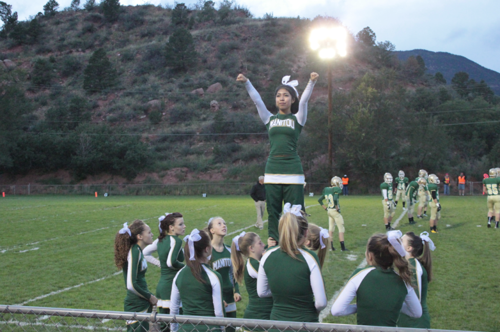 Cheer captain Susie Robbins demonstrates a lift at the Manitou v. Florence football game on Sept. 27