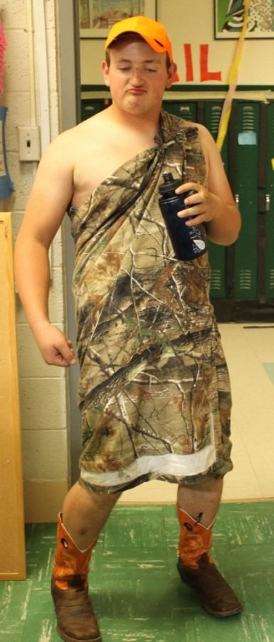 Cole Crumb (12) sports a camouflage toga paired with orange and brown cowboy boots.
