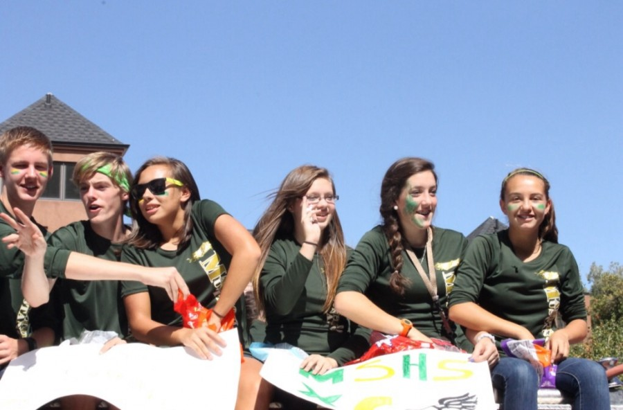 The cross country team smiles and waves to the observers and attendees at the parade.