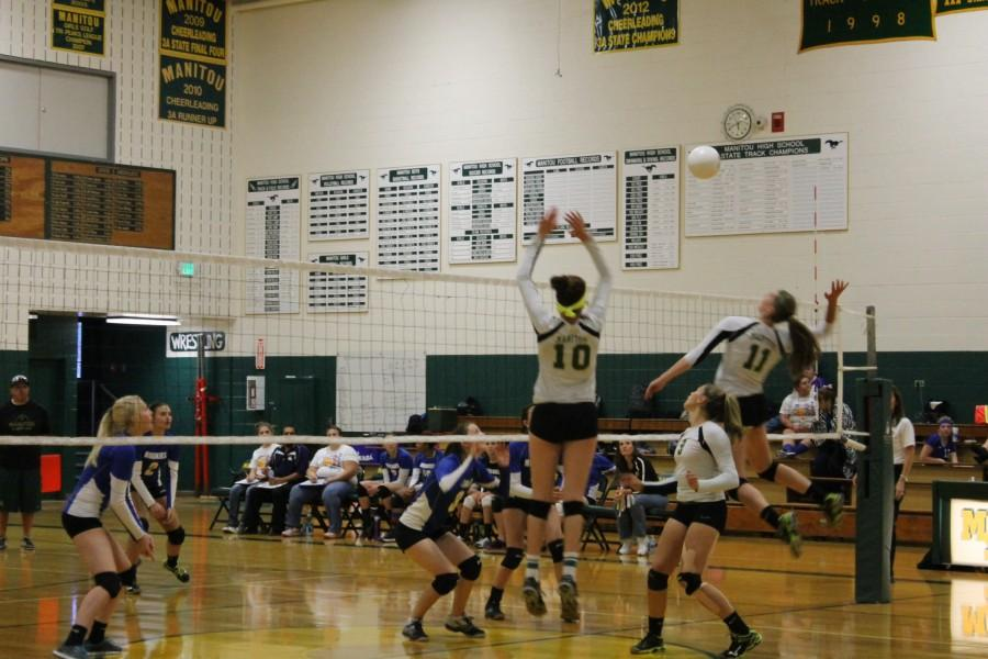 Katie McKiel (#11) and Brooke Garretson leap into the air- about to terminate a chance of Florence winning the game.