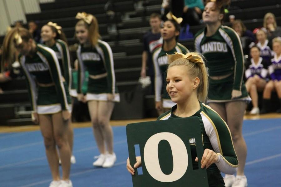 Stormy Garrigan (11) holds up the O in Manitou.
