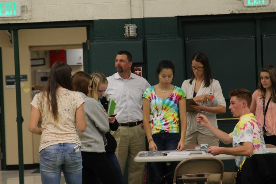 NHS (National Honor Society) members instruct arriving students and staff about the set-up and rotations at the drive.