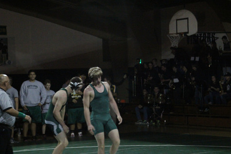 Billy Ryan (12) stands back up after pinning his opponent for the win.