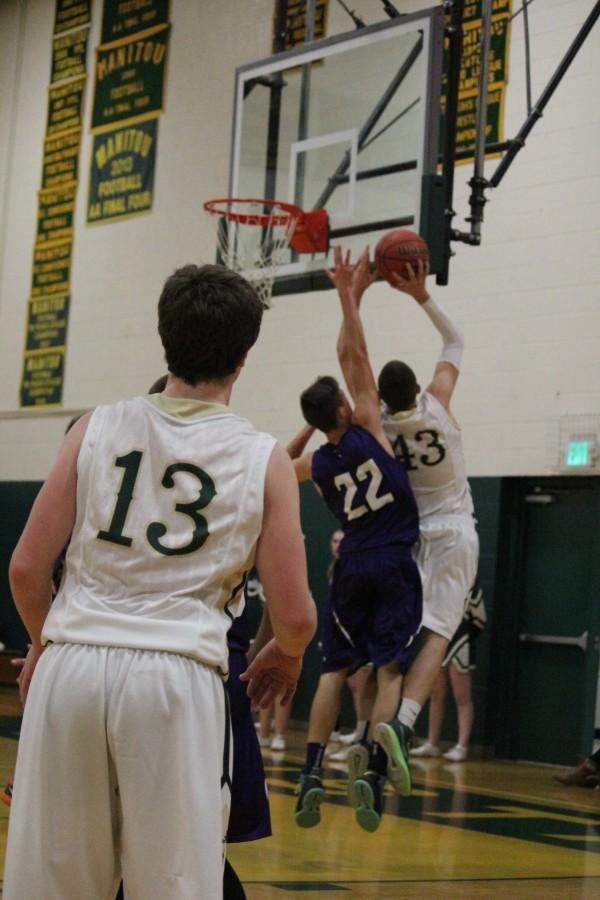 Senior Steven Jensen goes for a layup while Sophomore Davyn Adamscheck watches from behind.