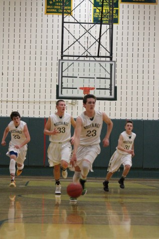 Sophmore Lucas Rodholm dribbles down the court with fellow teammates Danny McGee (12), Toby White (10), and Bryce Mcmillian (11).