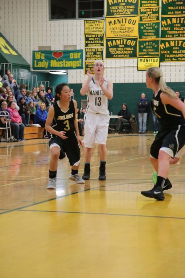 McKenzie Petricko shoots the ball amidst opposing players.