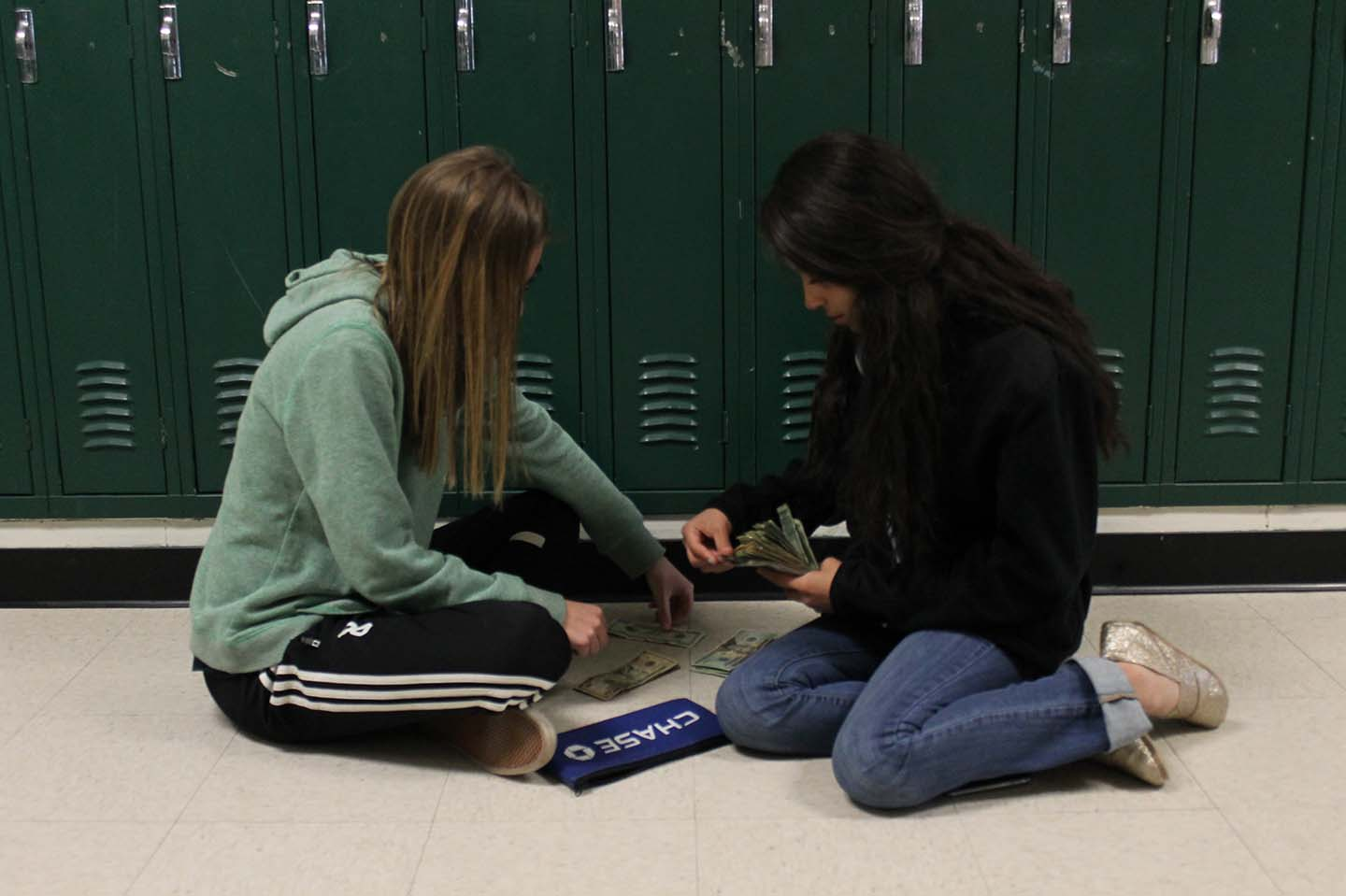 Kaitlyn Grieb and Blanca Blake count the funds raised by the selling of ayuda bands. The funds raised all go to supporting a Guatemalan child's education.