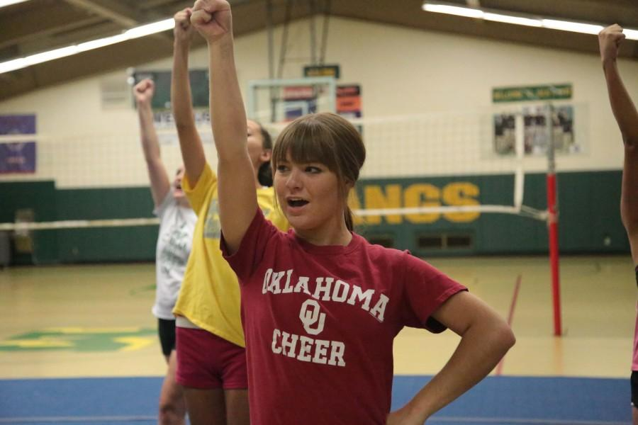 Ryan Murdock (12) leads a cheer at an early-season practice. The team has a new coach this year, Kaitlyn McTamney. McTamney hopes to change the aesthetic of the cheerleaders, making them more serious athletes and teaching them better technique.