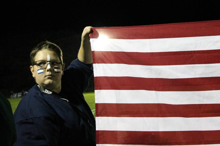 Ethan Carpenter (11) holds up an American flag during the bands half time showLast year, Woodland Park vandalized schools grounds, creating conflict between the two schools.