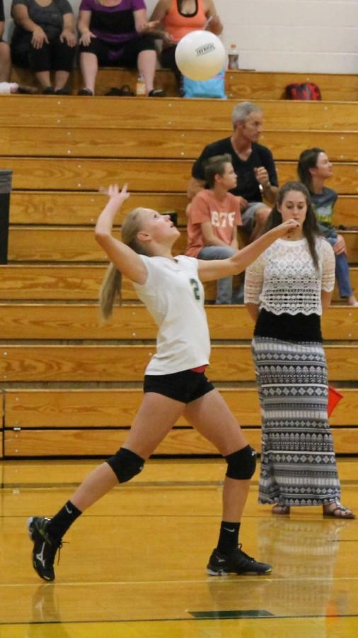 Olivia McKenna (9) serves the ball in their first game against James Irwin! People wait patiently on the sidelines to see what happens!