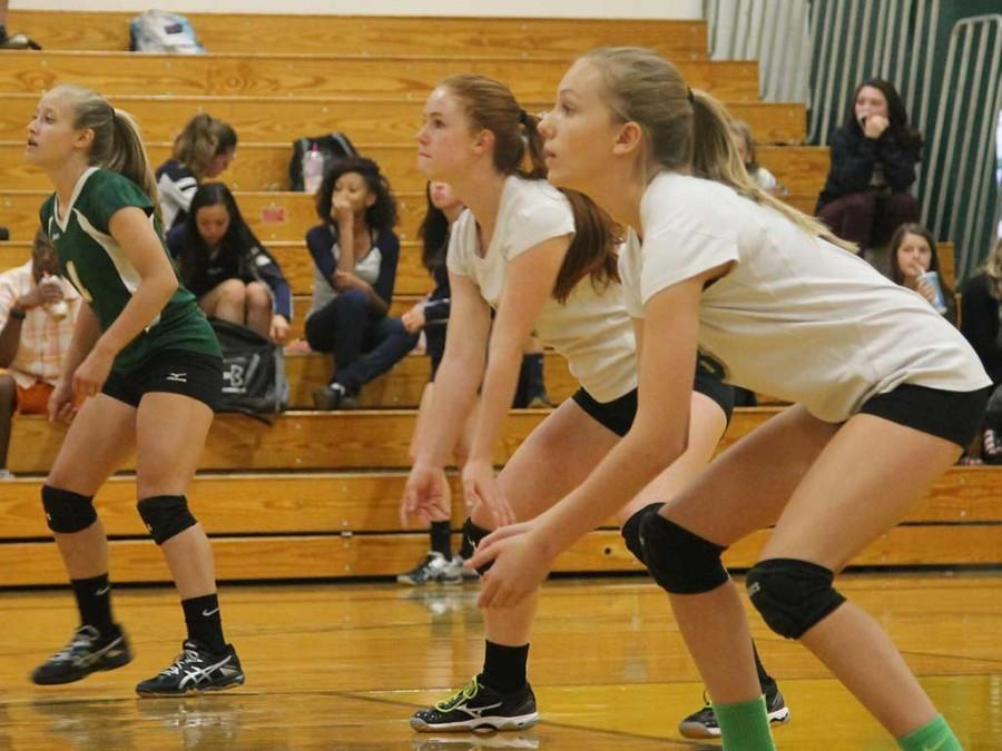 Alison Coleman (9), Ava Spangler (9), and Roxy Witham prepare for the volleyball coming over the net! Other team mates get read to help them out!