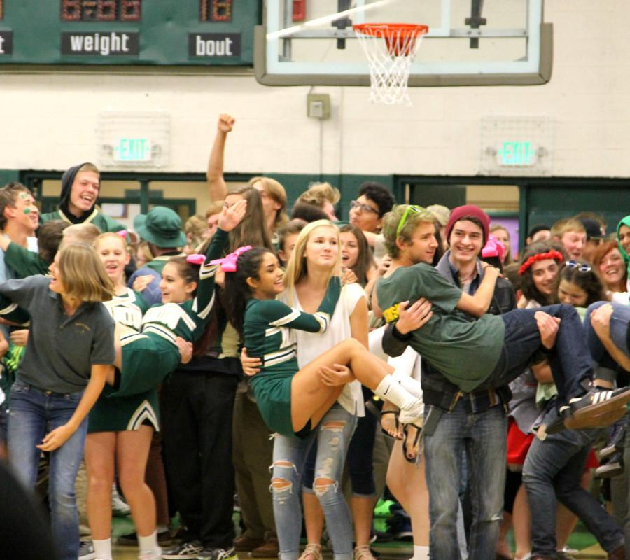 Bella Forcellini (12) and Austin Carlson-Sustarsic (12)  jump into the arms of Estelle Buth (12) and Taylor Mattson (12) during Ships N' Sailors at the homecoming assembly on October 9.