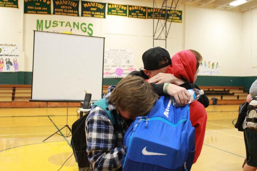 Sawyer Schroeder (10), Alliah Halcomb (10) and Bryce Coop (11) hug it out during the end of the assembly.