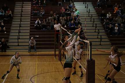 Senior+Brooke+Garretson+and+freshman+McKayla+Cully+jump+to+block+the+ball+coming+from+Windsor.+