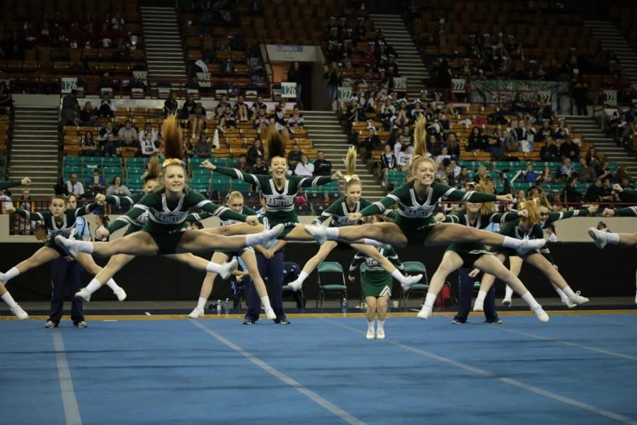 Ryan Murdock (12), Mahalia Henschel (12), and Kelsey Hartwig (12) lead the team in the completion of their jump sequence. All three girls have been on the cheer team since their freshman year.