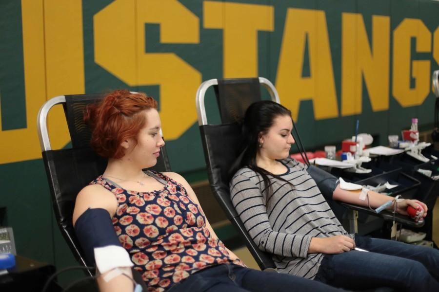 Seniors, Maddie Dayhoff and Sami Williams chat as they donate blood.
