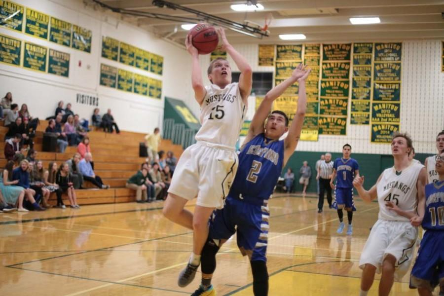 Cole Seinknecht (10) makes a two-point shot during the fourth quarter. Seinknecht scored a total of 14 points over the course of the game. In addition to being the only sophomore on the varsity basketball team, Seinknecht is the quarterback on Manitou's varsity football team.