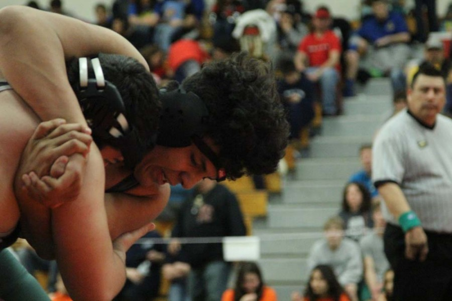 Julian Sanchez (11) struggles with his opponent trying to get down to the found to pin him. Sanchez placed third in his weight class and qualified for state.