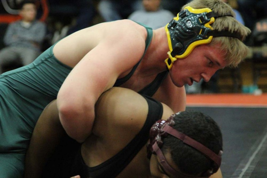 Atticus Fredrickson (11) struggles to pin his opponent. In this round Fredrickson pinned his opponent in 28 seconds. Fredrickson placed 3rd in his weight class and qualified for state.