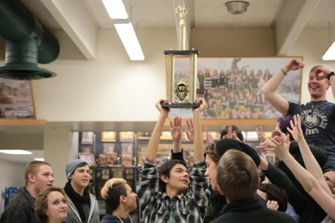 Matt Rivera (11) hoists the first place trophy above his head as the rest of the cast begins to cheer and reach toward it. Rivera has been heavily involved in Manitou's theatre department since middle school, and played a significant role in this year's fall play,