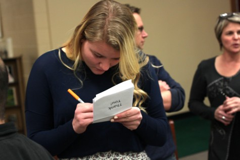 Kethrys Buffa (11) signing some of the thank you notes that were handed out to parents and coaches. Sadly Kethrys will not be able to swim next year.