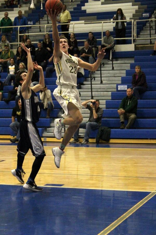 Lucas Rodholm(11) goes up for a layup against James Irwin at Districts. The Mustangs won this game and went on to win the next, which gave them the league title. They will play at the Regional Tournament on Friday, March 4.