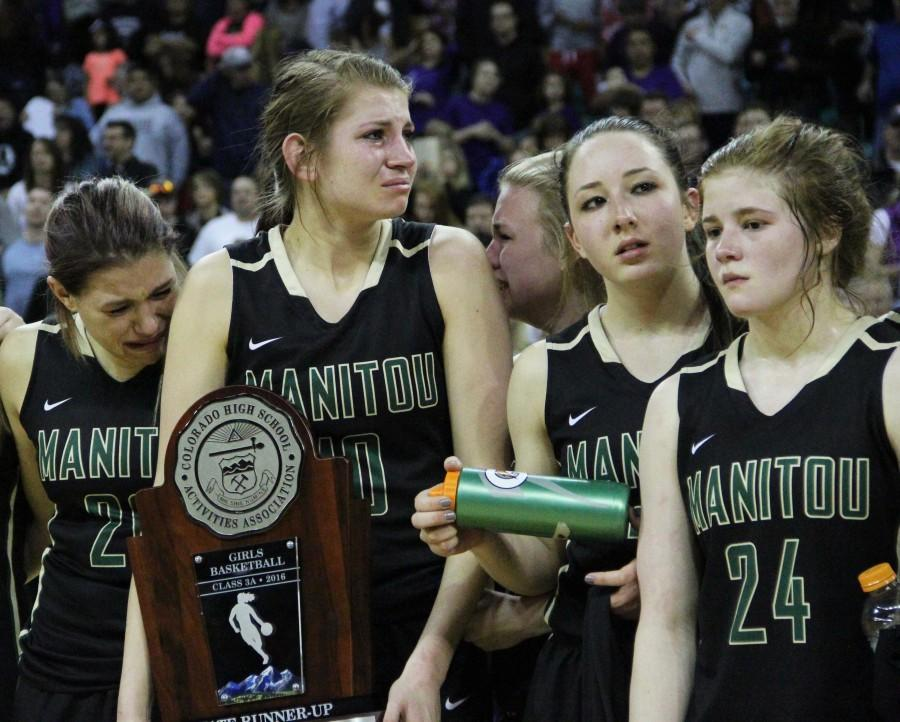 Upon being named the girls basketball state runner-ups, Angala Jensen (12), Brooke Garretson (12), Ariana Olsen (11) and Shelby Megyeri (11) gather for a group photo. As Garretson holds the trophy, she and fellow senior teammate  Angala Jensen attempt to hold back tears. The two have both been playing varsity volleyball and basketball at Manitou for several years, this being their last time on the court together while in high school.