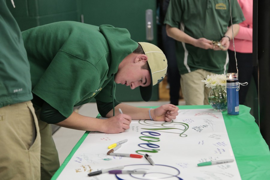 Lucas Culver (11) signs a banner that was set out as part of the remembrance assembly. After the assembly had ended, many students made their way into the commons to sign the banner, and by the time most students had left, it was nearly full of signatures and messages for Ryan Lanosga.