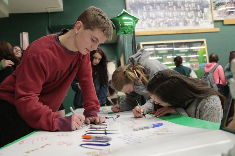 Tanner Weber (12) signs Lanosga's remembrance banner. The banner, which was filled with students' signatures, will serve as a tribute to Lanosga.