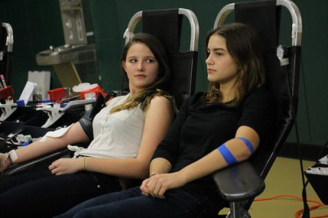 Kylie Middleton (10) and Brooke Hackelberg (12) donate blood side by side. This is Kylie's first time donating blood, and one of the few sophomores to do so.