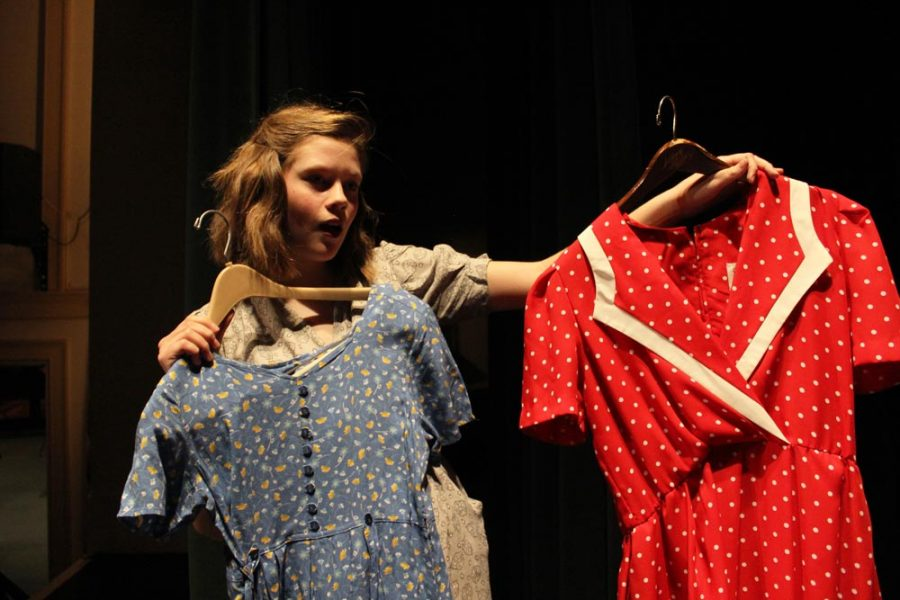 Grace (Maggie Anderson) tries to decide which dress to wear to court.
