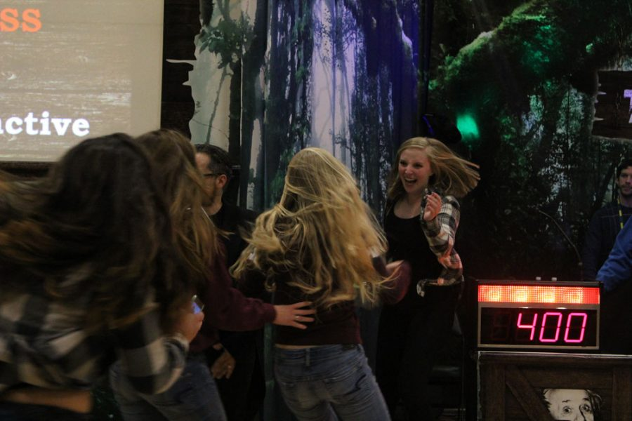 Cassie Riley (11) runs to hug her teammates after winning the final round of the assembly, along with $100 in iTunes gifts cards. Answering all three parts of an orchestra won Riley the competition.