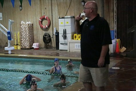 Roy Chaney, the head coach, gives the girls their warmup after telling the girls their lineup for the next day's meet.