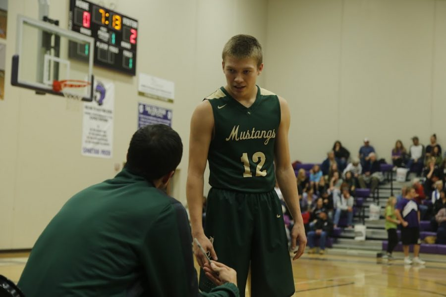 Cole Sienknecht (11) listens to coach Brian Vecchio before going back onto the court. Vecchio has been a Manitou coach for about ten years now.