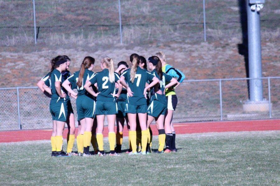 The team huddles up during a game against Pagosa High School. The Mustangs won  6-0.