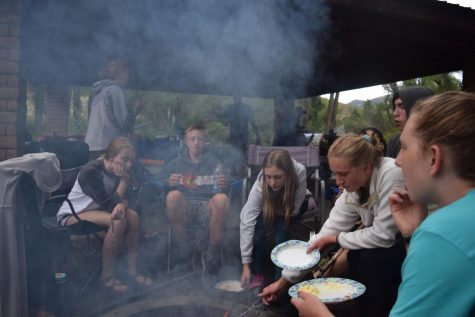 Lizzy Butts (10), Parker Hall (10), Mia Heiniger (9), Jayden Omi (11), Sage Stevens (12) and Coco Stevens (10) gather around a fire to converse and cook hot dogs in the evening.
