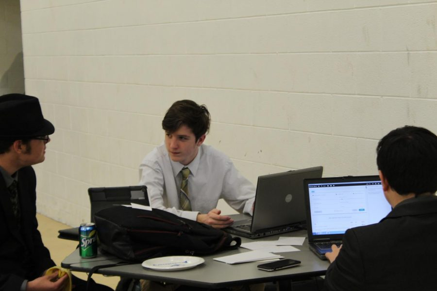 Jake Underwood (11), Tyler McCune (9), and Taylor Knight (10) gather research for their topic to present a case in front of the panel of judges. They are given 30 minutes to take in information from articles and make a point.