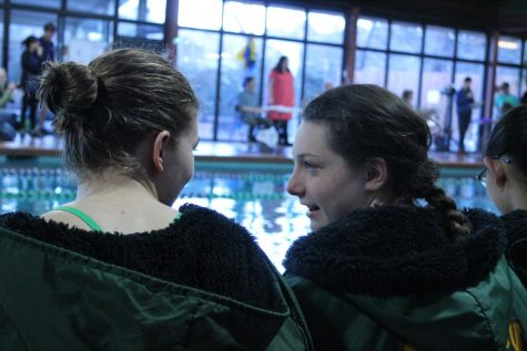 Emily Combs (9) and Caroline Maestas (9) chat besides the pool during diving. After diving ends, the team gets together for their