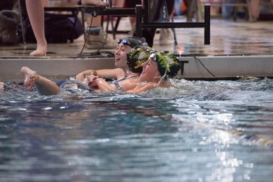 Coco jumps over two lanes to congratulate her sister after racing in the finals heat at the Tri-Peaks League meet. Racing each other in the 50 free was not a rare occasion this season, as it is both of the girls' best event.