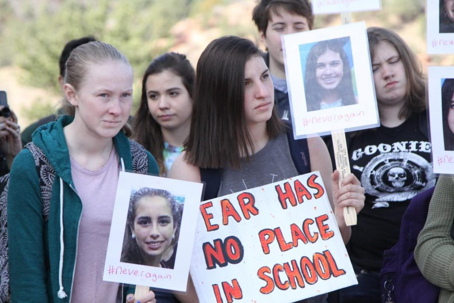 Students Abby Pribilla (9) and Dominique Ortonword (11) stand holding signs with the faces of victims from the Florida school shooting. The leaders of the Walk-Out made signs for participants to hold up during the event, but many students made their own as well.