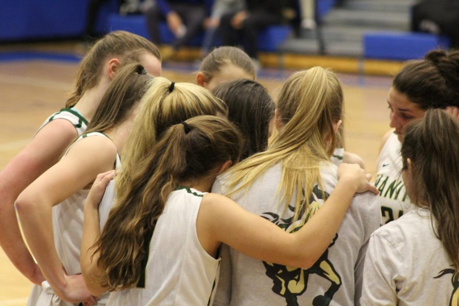 The+Mustangs+huddle+up+to+go+over+an+inbounds+play+in+the+third+quarter.+During+the+time+out%2C+Brooklyn+Mack+%2812%29+showed+love+for+her+teammates+Amanda+Nagel+%2812%29+and+Courtney+Brown+%2810%29.