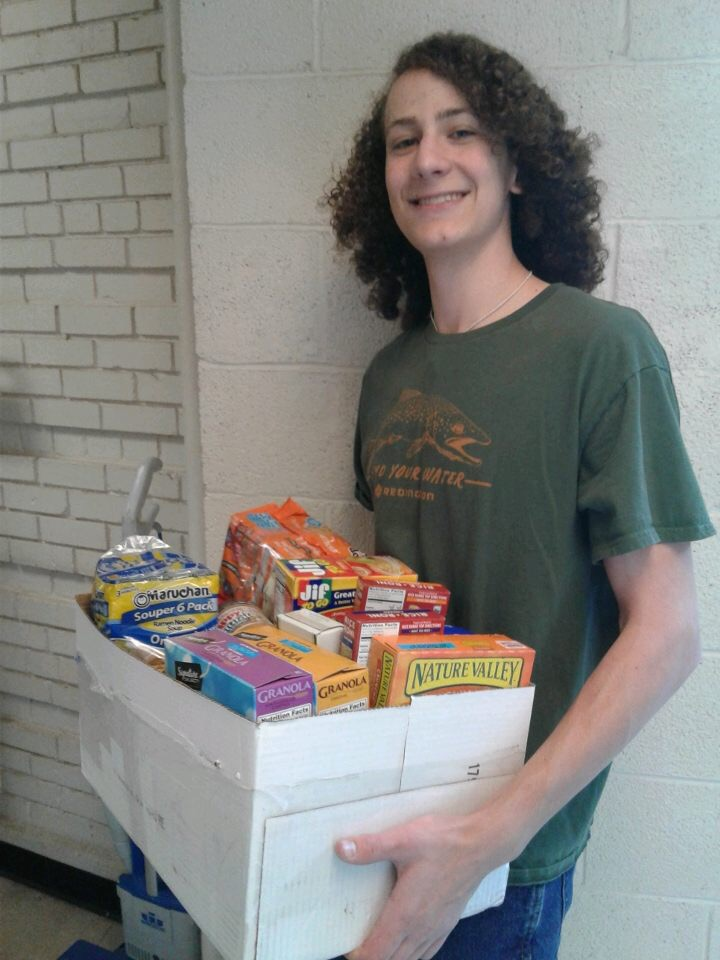 Ben Schwartz (11) carries a box of donated food items into the food pantry to unload at the end of the day.