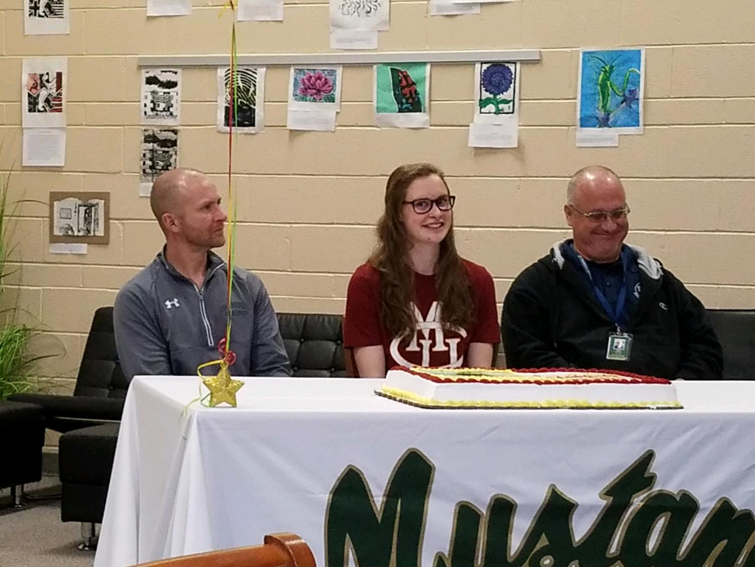 Sydney Dolloff-Holt (12) signs with MSHS Athletic Director Cameron Jones and Colorado Torpedoes Head Swim Coach Roy Chaney present. Dolloff-Holt will attend Colorado Mesa University in the fall.