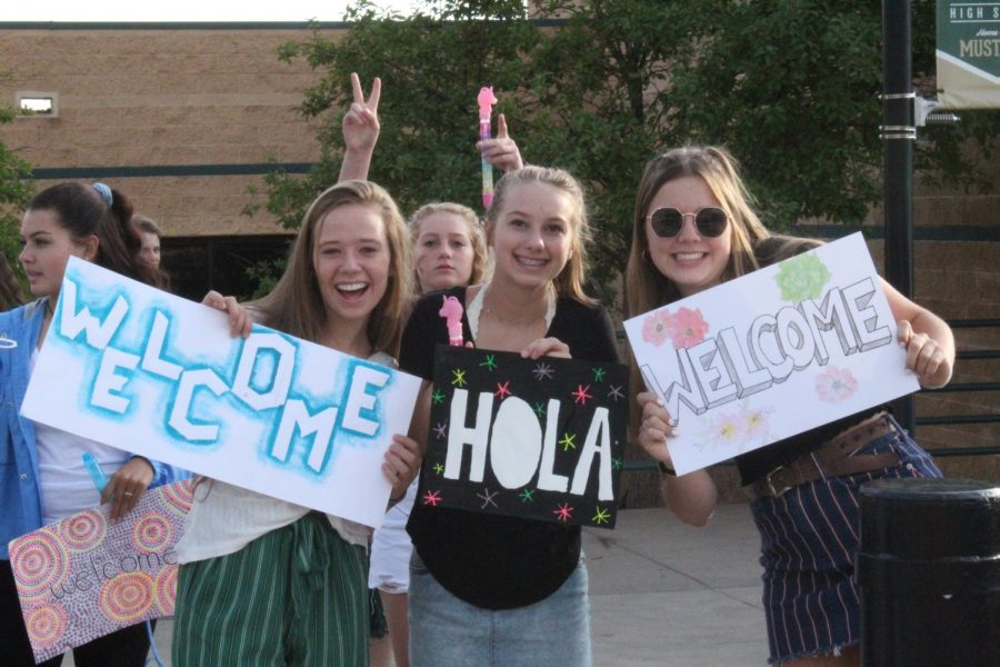 Abigail Parker (10), Norah Jorstad (9) and Mahlia Glass (11) hold signs when greeting students on the first day of school.
