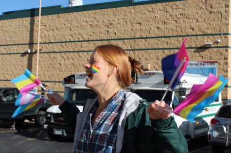 Abigail Kilpela (11) holds LGBTQ flags, dances and shows her kindness while welcoming students to school on Monday morning.