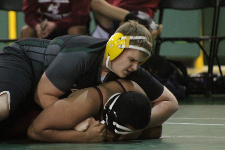 Connor Durfee (10) works to roll his Sand Creek opponent onto his back for a pin.