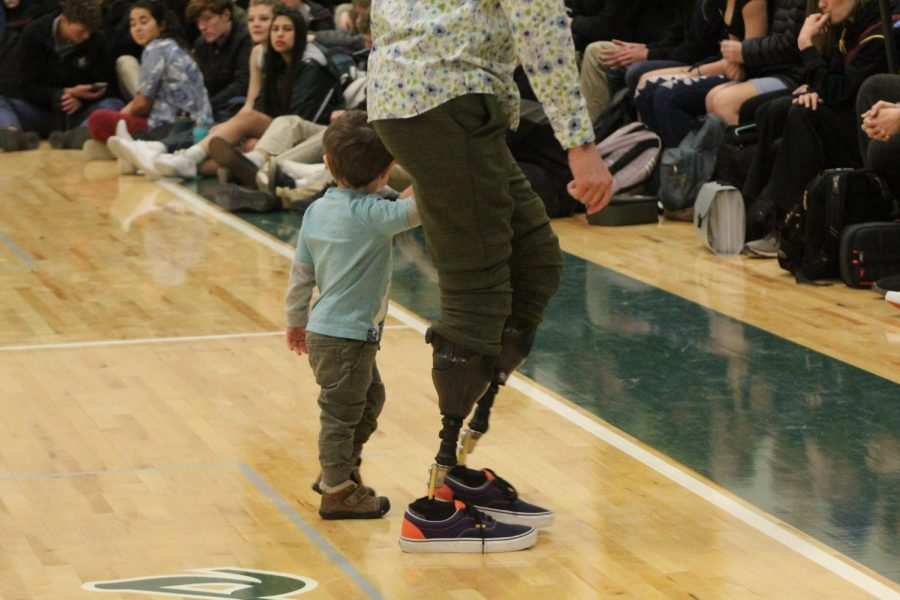 Mr. Noland walks hand in hand with his youngest son, Ben, after speaking during the assembly.