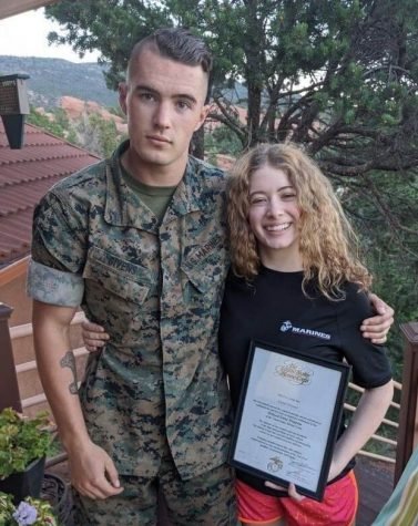 Laine Givens (12) poses with her brother Cade Givens (Class of 2019) and her Marine Corps contract.