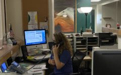 Stacy Thomson, in her new office, answers the phone and signs in students at the beginning of the 2021-2022 school year.